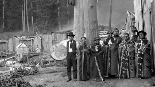 Eight members of the Kwakiutl First Nations are photographed outdoors in traditional dress and face paint, circa. 1895 – 1898. The man on the leftmost side holds a large drum.