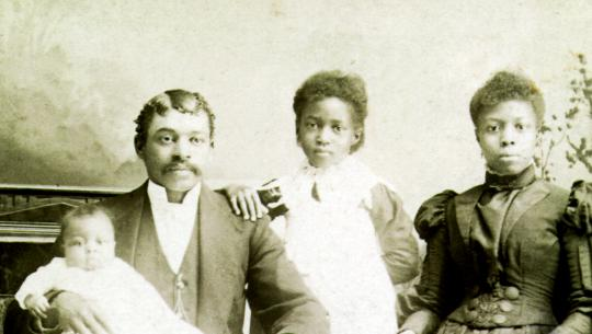 A Black couple and their two young children – one school-aged daughter and an infant – pose for a family portrait, circa. 1850s. They are dressed in typical Victorian-era fashion.