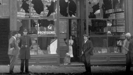 Following the Vancouver anti-Asian riot in September 1907, the storefront of Nishimura Masuya's grocery store is damaged with shattered windows. Onlookers include a police officer, an Asian woman in the doorway of the store, and a South Asian man.