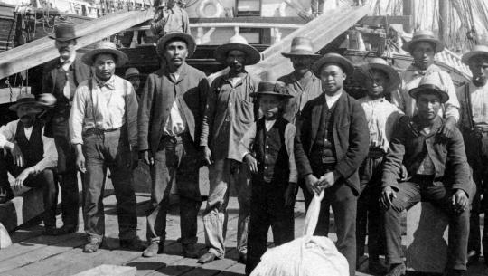 A group of longshoremen – composed of South Americans, Asians, Europeans, and Indigenous People –  pose for a photograph on the docks of Moodyville, circa. 1889. Included are Joe Capilano and William Nahanee.